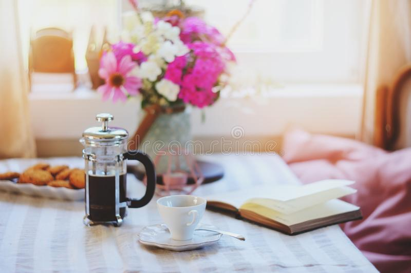 Summer breakfast in cozy country house. Table with bouquet of flowers from own garden, french press with coffee and cookies. Happy life royalty free stock image