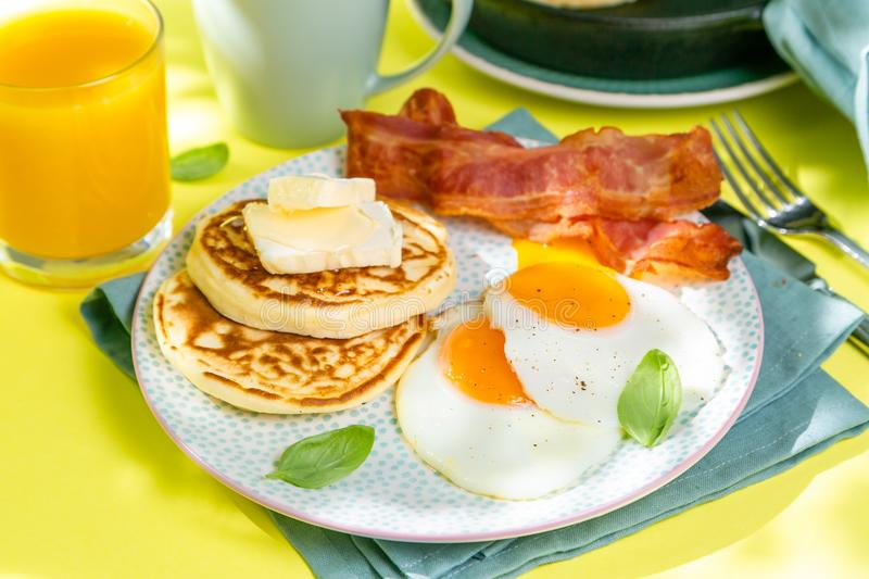 Summer breakfast - eggs, bacon, pancakes, cereal stock images