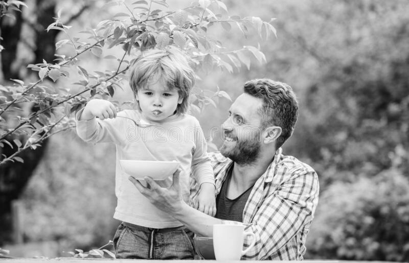 Summer breakfast. Healthy food concept. Feeding baby. Menu for children. Family enjoy homemade meal. Father son eat food stock image
