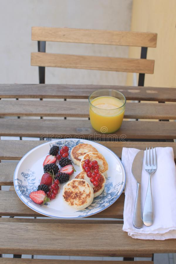 Summer breakfast on terrace or balcony Travel morning Traditional breakfast Cottage cheese pancakes with berries and orange juice royalty free stock images