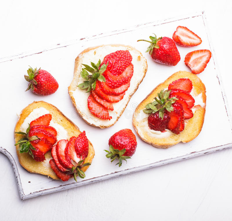 Summer breakfast. Toasts with butter and strawberry royalty free stock photography