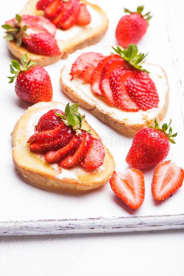 Summer breakfast. Toasts with butter and strawberry royalty free stock images