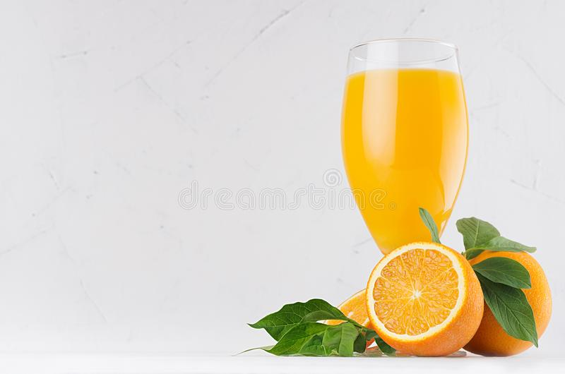 Summer bright citrus juice with group oranges, round slice and young green leaves on white modern kitchen interior. stock images