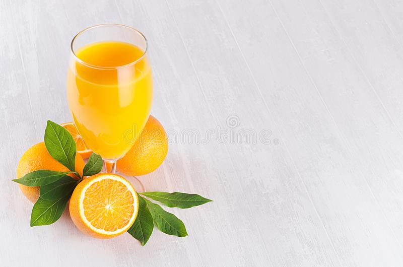 Summer bright citrus juice with group oranges, round slice and young green leaves on white wood board, top view, copy space. royalty free stock photo