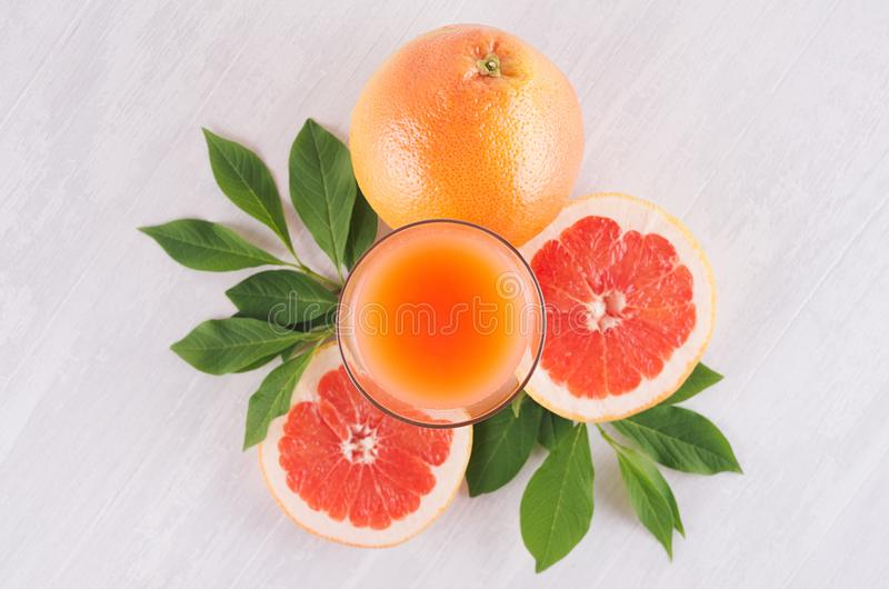 Summer bright fresh pink cocktail of grapefruits with green leaves, slice grapefruit on white wooden background, top view. stock photos