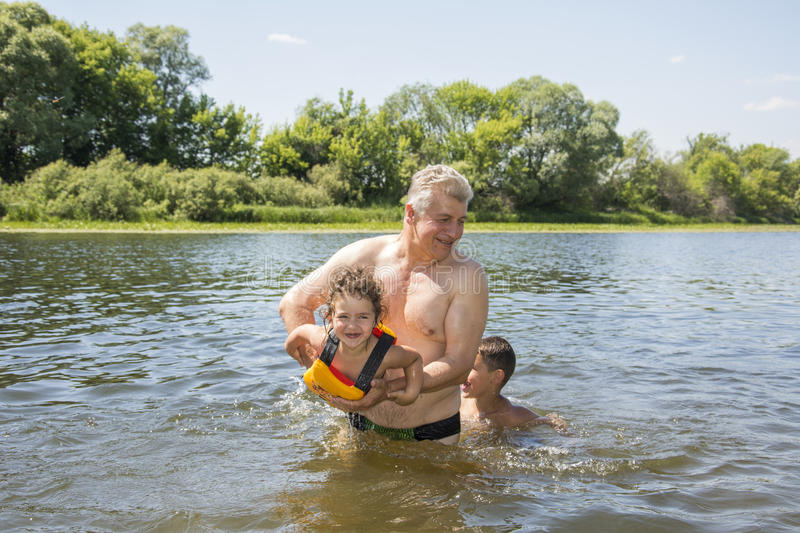In summer, on a bright, sunny day on the river, grandfather teaches her granddaughter to swim. In summer, on a bright, sunny day on the river, grandfather royalty free stock photography