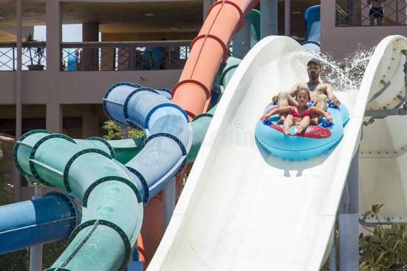 In the summer, on a bright sunny day, in a water park, father and daughter slide down the hill stock image