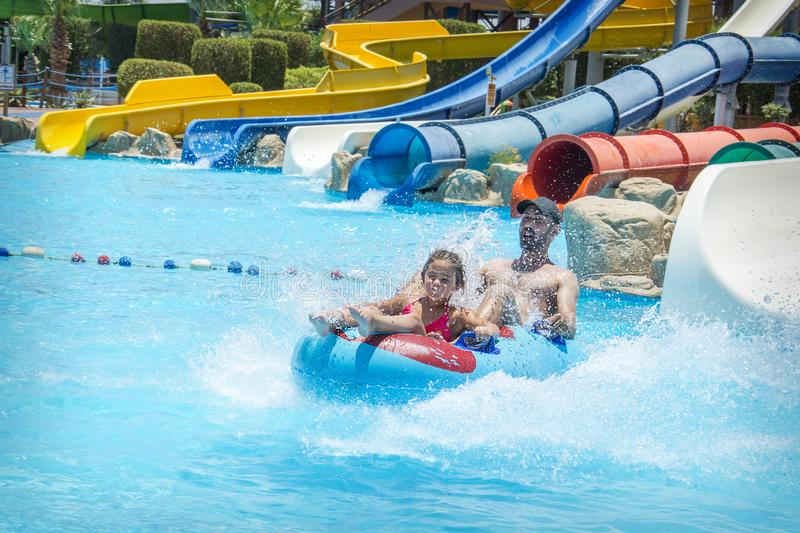 In the summer, on a bright sunny day, in a water park, father and daughter slide down the hill royalty free stock image
