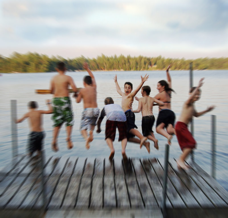 Summer camp blur. An action blur of a group of eight kids ages 11-13 jumping off on a dock into a lake at summer camp
