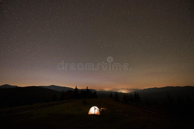 Summer camping at night. Tourist tent and burning campfire on green valley under dark starry sky. stock image