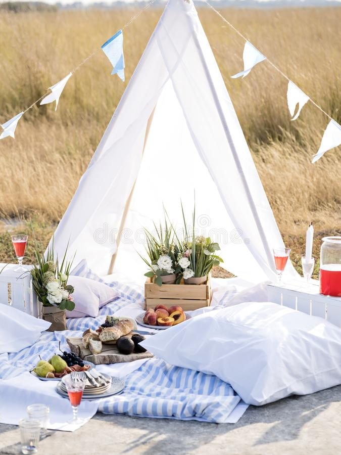 Summer camping scene. Summer brunch or dinner organized on a sea shore for friends. Elegant decorated place for romantic date. Sun lit flowers, fruits, cheese stock photo
