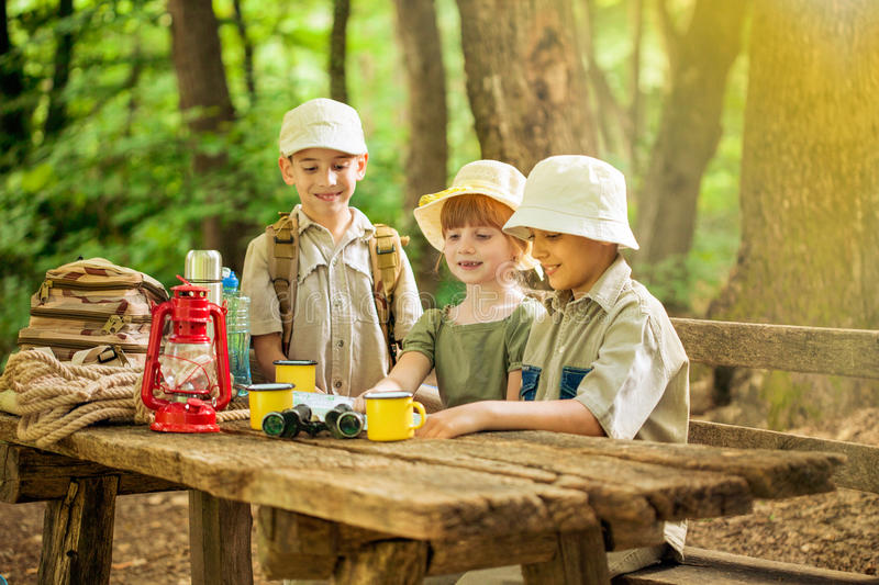 Summer camps,scout children camping in nature. Little boys and girl go hiking with backpacks on a forest road bright sunny day stock photo