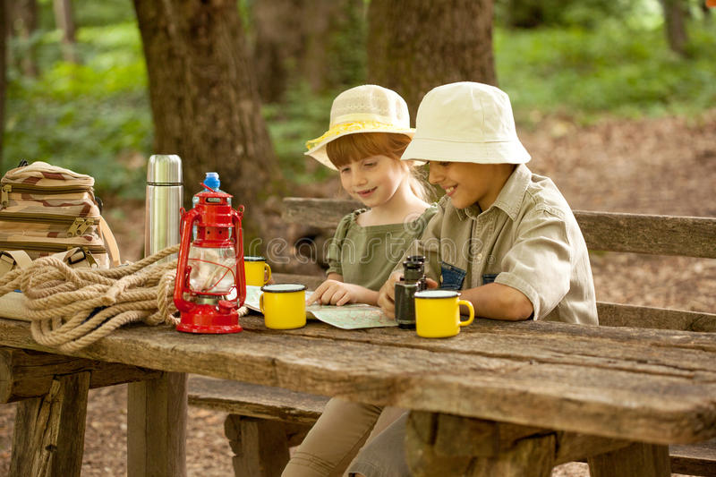 Summer camps,scout children camping and read map. Little boy and girl go hiking with backpacks on a forest road royalty free stock images