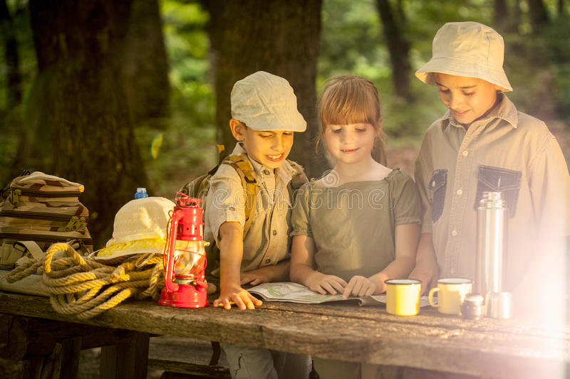 Summer camps,scout children camping and read map. Little boy and girl go hiking with backpacks on a forest road royalty free stock photo
