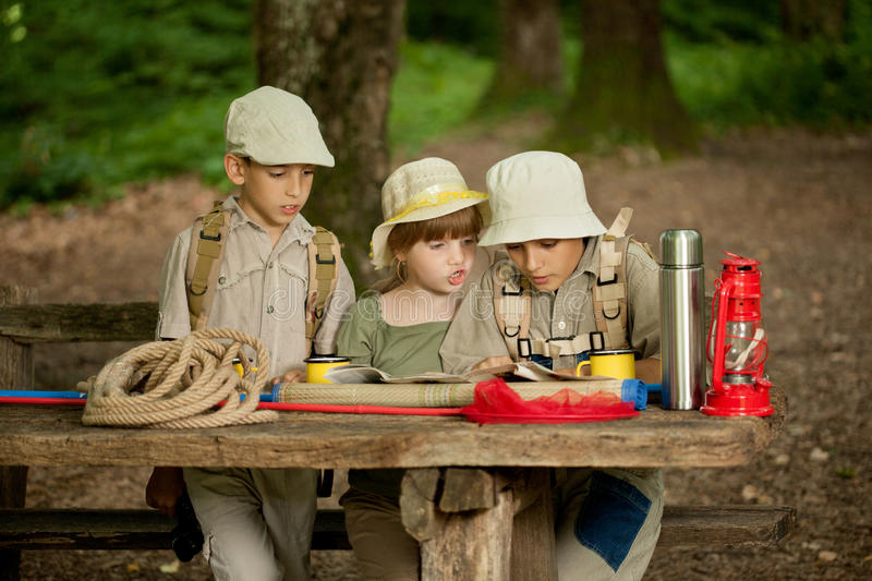 Summer camps,scout children read map. Little boys and girl go hiking with backpacks on a forest royalty free stock photos