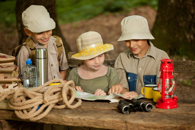 Summer camps,scout children read map. Little boys and girl go hiking with backpacks on a forest royalty free stock photography