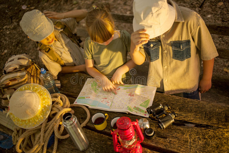 Summer camps,scout children read map. Little boys and girl go hiking with backpacks on a forest royalty free stock photo