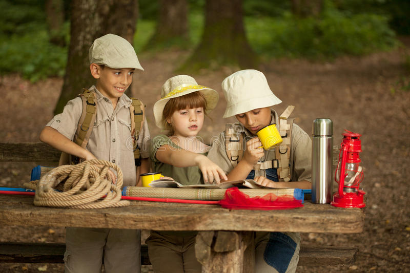 Summer camps,scout children read map. Little boys and girl go hiking with backpacks on a forest royalty free stock images
