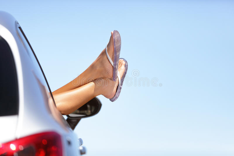 Summer car road trip vacation fun woman feet out. Summer road trip car vacation fun. Woman legs out the car window in blue sky background. Carefree, freedom stock photos