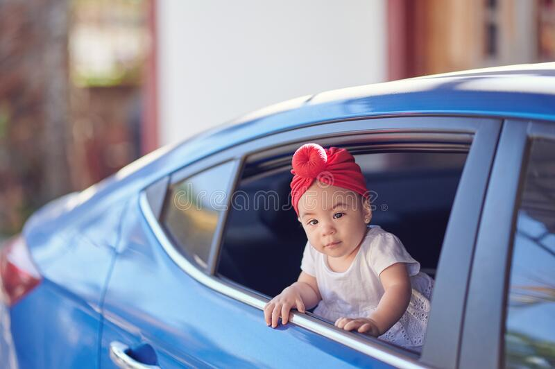 Summer car trip theme. Little passenger looking out from car window royalty free stock photography