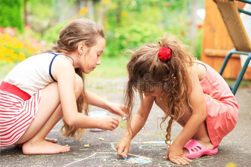 Summer, childhood, leisure and people concept - happy little Girls is drawing with chalks on summer park. Summer, childhood, leisure and people concept - happy stock images
