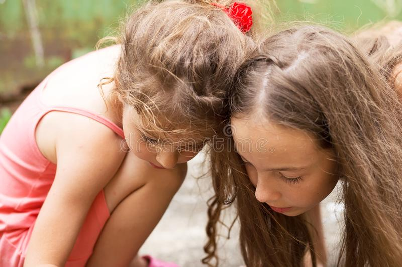 Summer, childhood, leisure and people concept - happy little Girls is drawing with chalks and playing on summer park royalty free stock photo