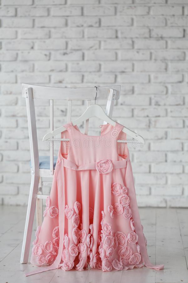 Summer children`s dresses hang on hangers on the back children`s chair. Place for text stock photos