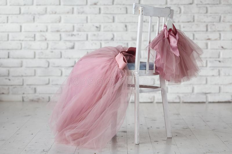 Summer children`s dresses hang on hangers on the back children`s chair. Place for text royalty free stock images