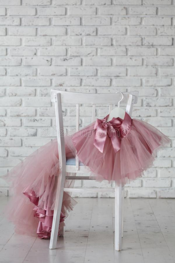 Summer children`s dresses hang on hangers on the back children`s chair. Place for text royalty free stock photos