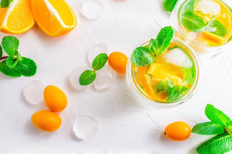 Summer citrus drink with orange, kumquat, mint and ice cubes on white background. Flat-lay, top view stock photos