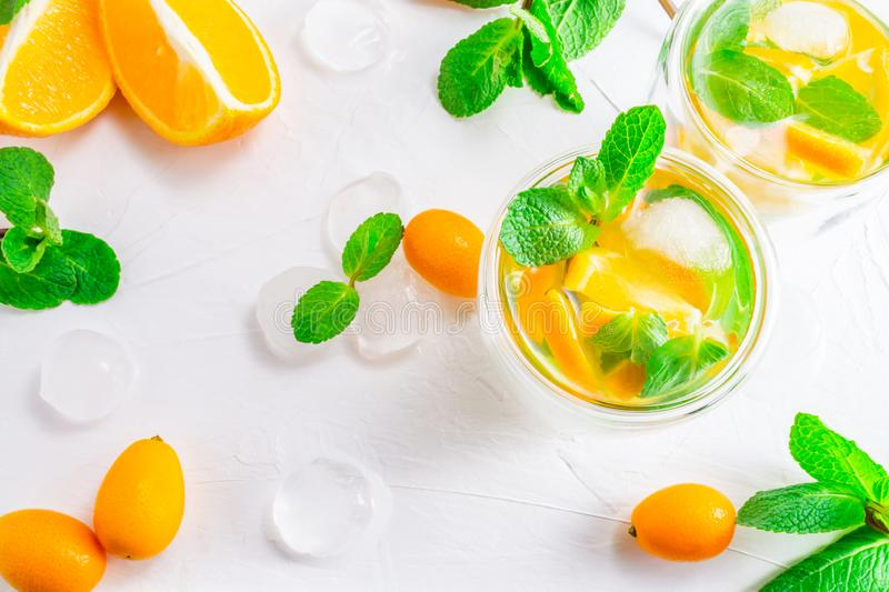Summer citrus drink with orange, kumquat, mint and ice cubes on white background. Flat-lay, top view stock photography