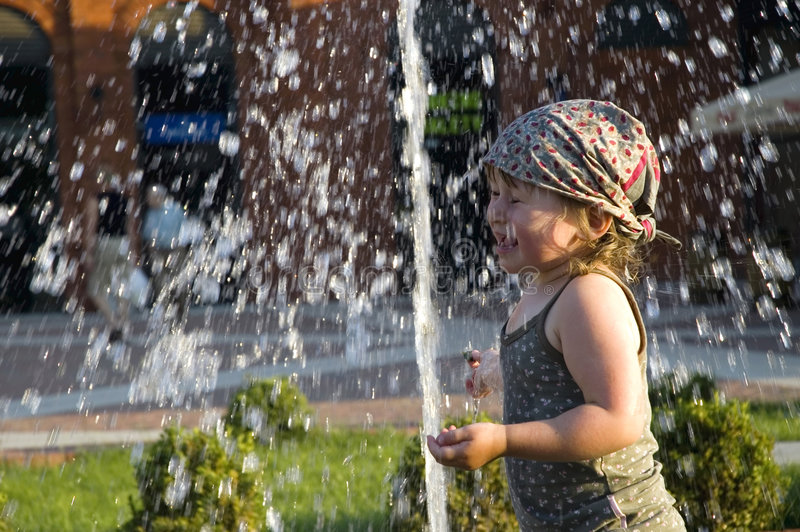 Summer in the city. Child playing in a public fountain. summer scenic royalty free stock photo