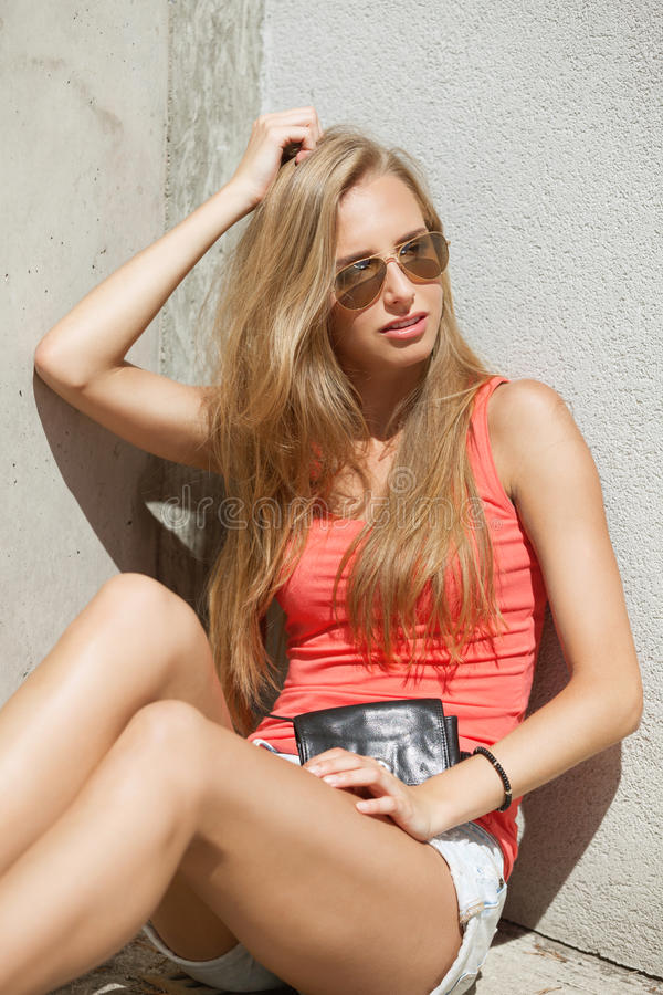 Summer in the city. Exhausted girl is waiting through the heat in the city royalty free stock image