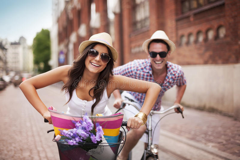 Summer in the city. Happy couple cycling in the city