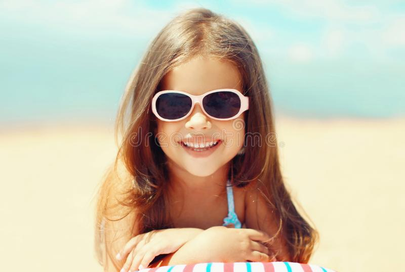 Summer close-up portrait smiling child little girl lying on beach stock image