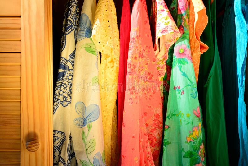 Summer clothing in a closet. Colorful summer shirts hanging in a wardrobe royalty free stock image