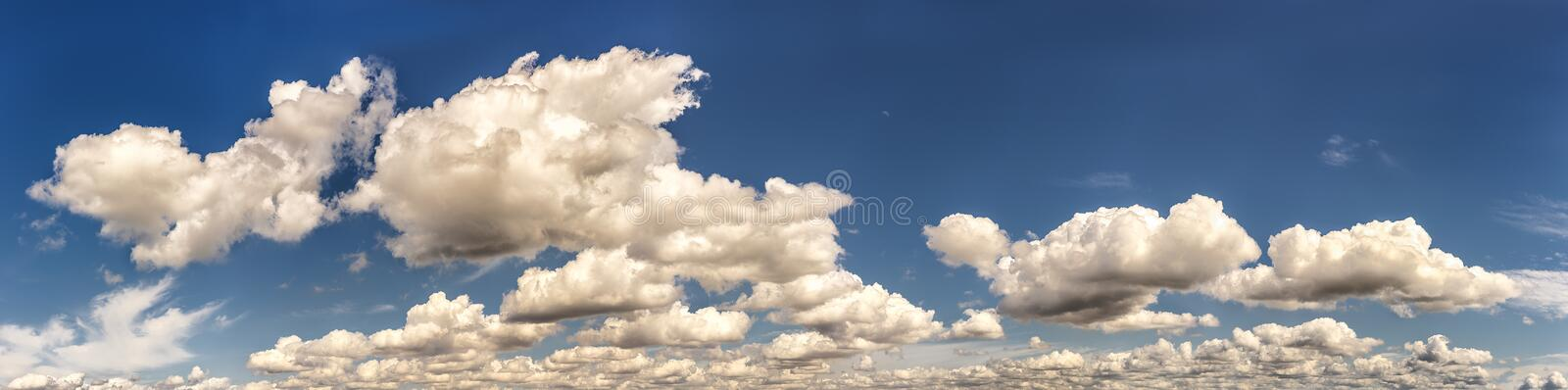 Summer clouds panorama with moon. Fluffy white summer clouds dance across a sky panorama with moon setting in background stock photography