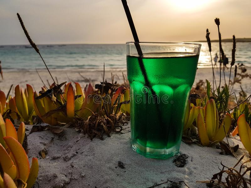 Summer cocktail on the beach at sunset. Mint-based cocktail ready to be sipped by the sea royalty free stock photos