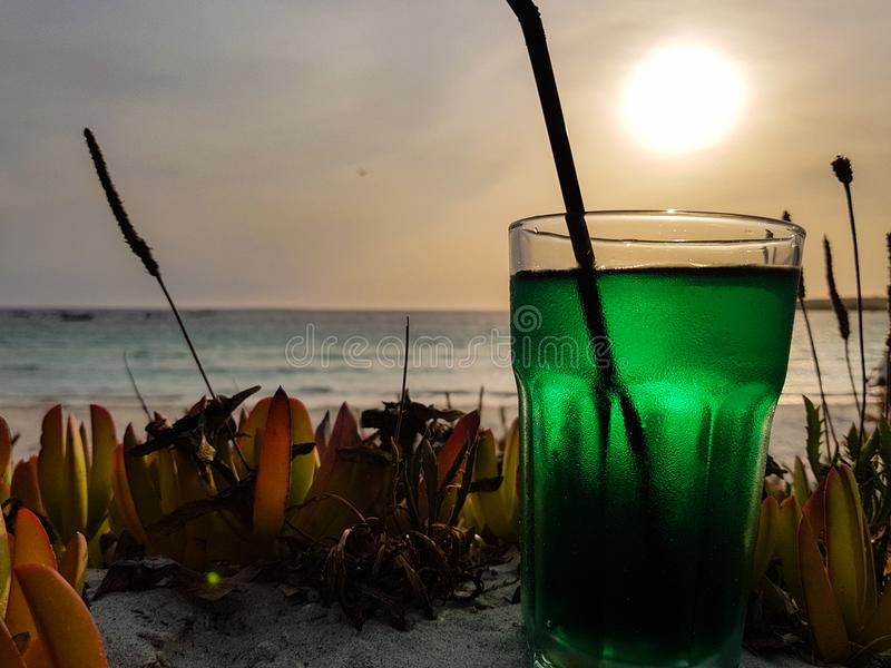 Summer cocktail on the beach at sunset. Mint-based cocktail ready to be sipped by the sea stock photos