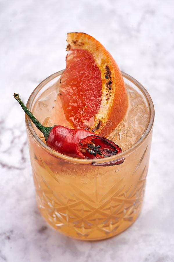 Summer cocktail concept. Fresh sweet orange cocktail with slice of roasted orange and red pepper royalty free stock images