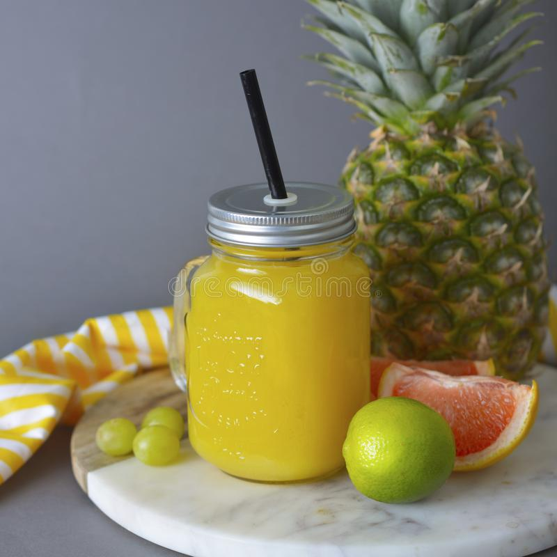 Pineapple cocktail or juice in glass jar bottle with straws and fruits on background - pineapple, oranges, grapefruit, lime and stock image