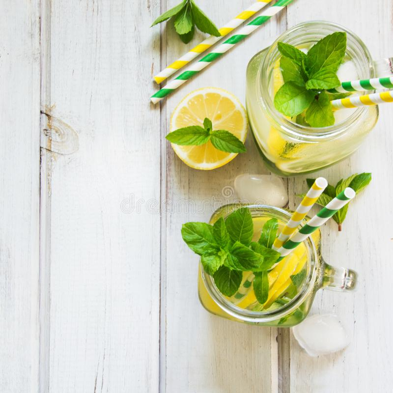 Summer cocktail, water detox with lemon, ice and mint in mason jar on a white wooden background. Top view. royalty free stock photo