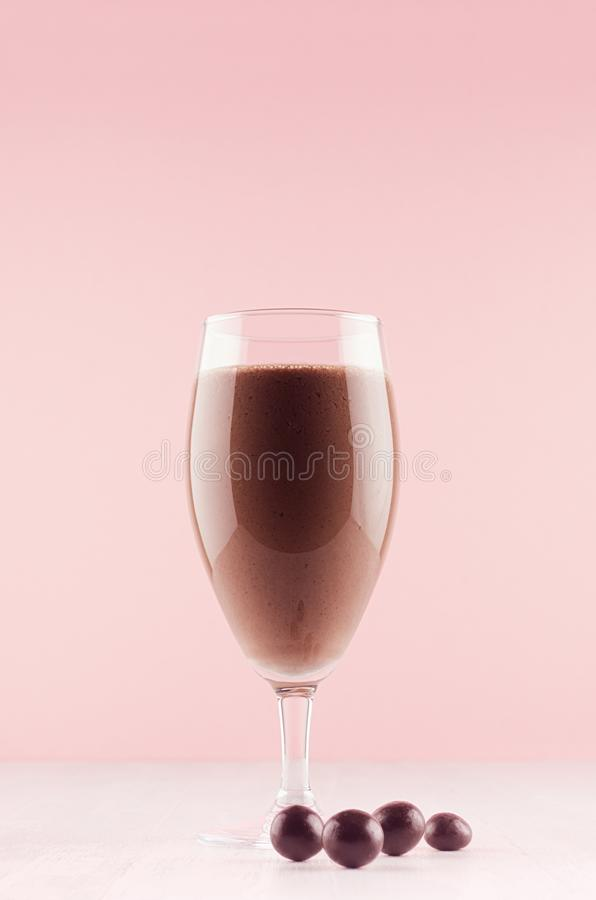 Summer cold fresh milk cocktail of cacao with chocolate candy on white wood board and cute soft pastel pink wall, vertical. Summer cold fresh milk cocktail of royalty free stock image