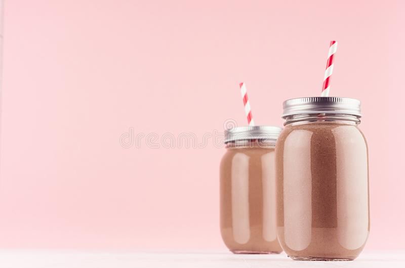 Summer cold fresh milk cocktail of cacao in jars with straw, silver lid on white wood board and cute soft pastel pink wall. stock image