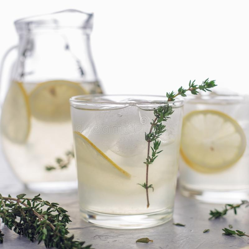 Summer cold fruit infused water with lemon and thyme in the glasses and jug on the table. royalty free stock photography
