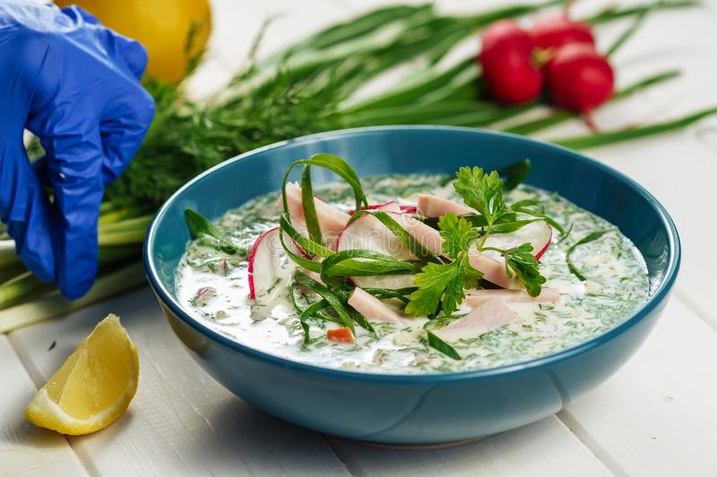 Summer Cold Yogurt Soup Okroshka Chefs Hand Side. View. Russian Radish and Cucumber Healthy Cuisine with Green Onion and Dill Close-up for Recipe Ingredient royalty free stock photography