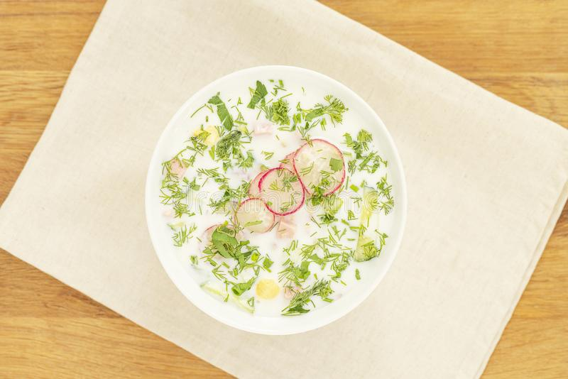 Summer cold yogurt soup okroshka. Traditional Russian soup okroshka in bowl on wooden background. Top view royalty free stock image