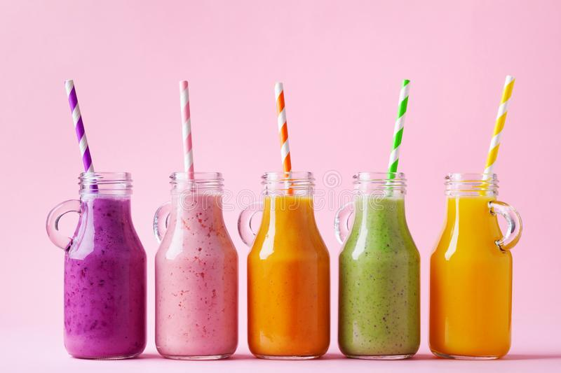 Summer colorful fruit smoothies in jars on pink background. Healthy, detox and diet food concept royalty free stock photos