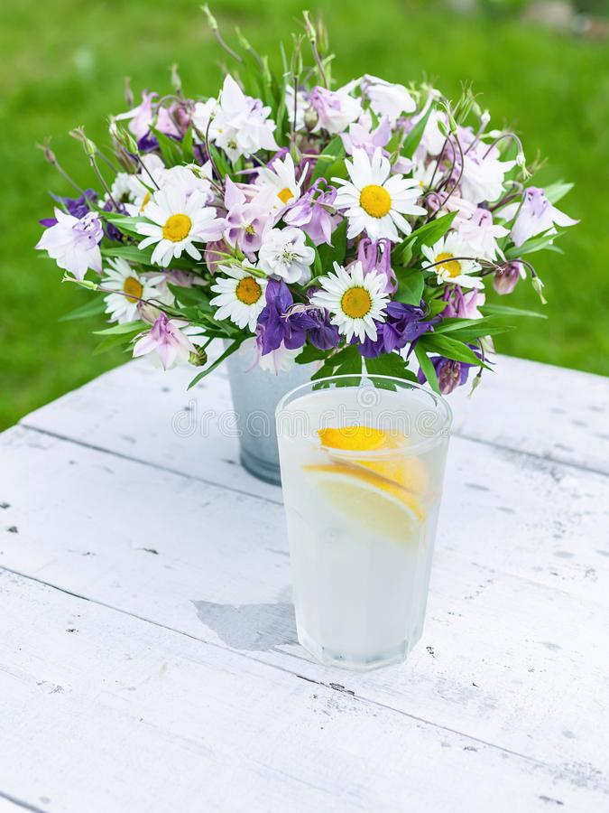 Summer composition. Bouquet of wild flowers, cold lemonade on a rustic background. Vertical shot royalty free stock photo