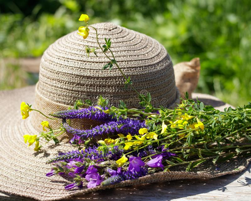 Summer composition. A bouquet of wild flowers and women`s sunhat. stock photo
